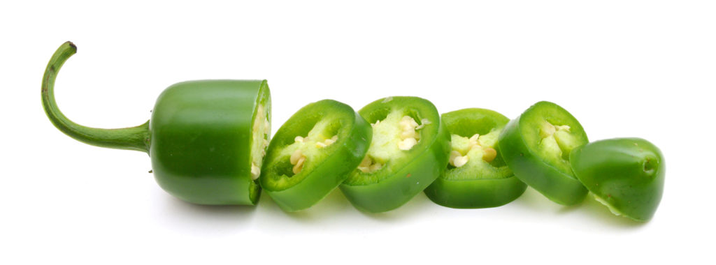 A green jalapeno on a white background, sliced with each piece laying in a line.