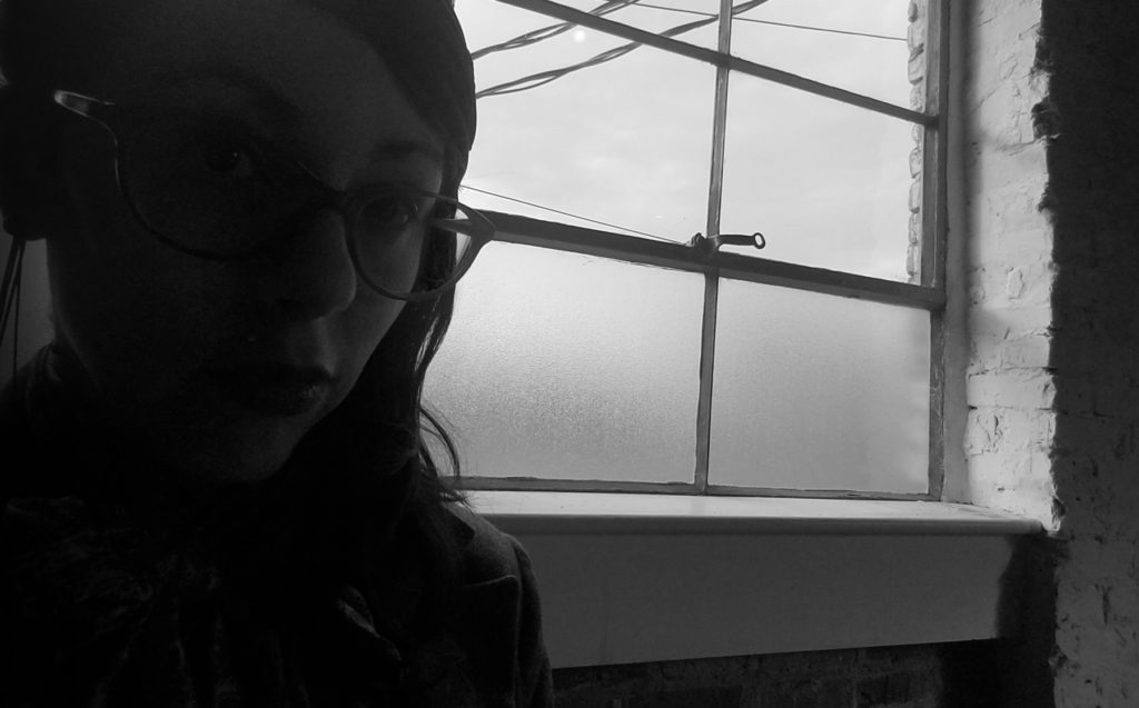 A. Almond-Harvey seated in front of a window overlooking a cloudy day, in shadows.