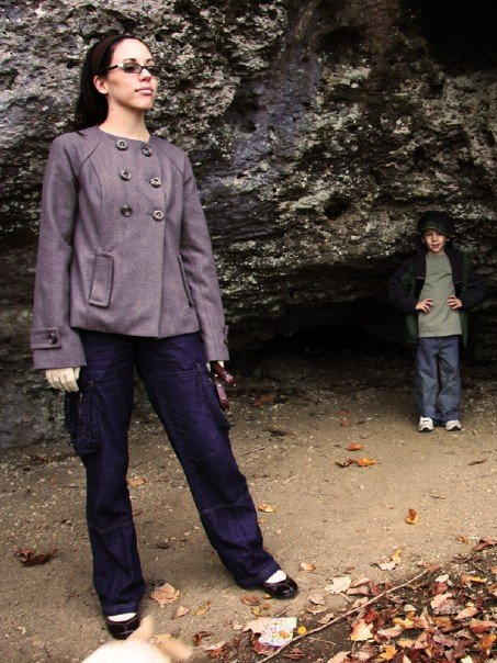 A woman in a brown-gray coat standing on a walkway under a rock outcropping, holding a dog leash. A small child is standing in the background.