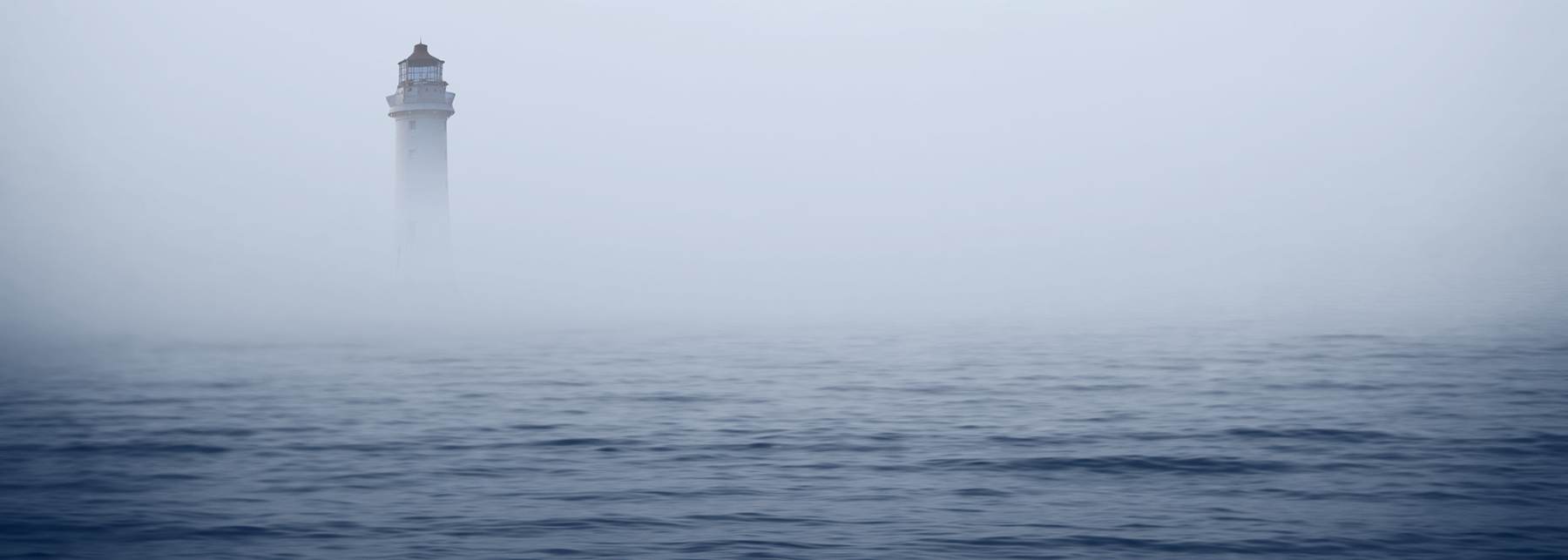 Image of a lighthouse in the fog, which obscures the shoreline. The ocean is calm but dark.