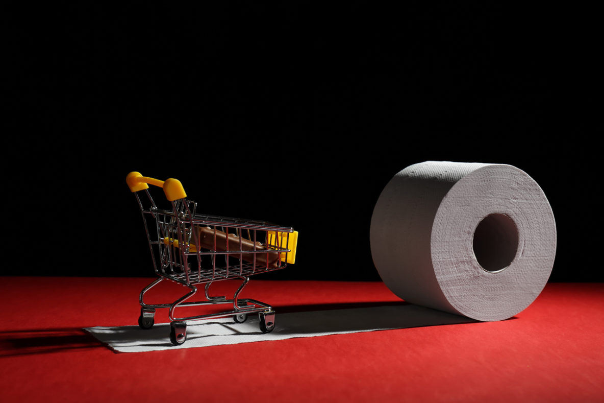 Roll of toilet paper and small shopping cart on table against dark background